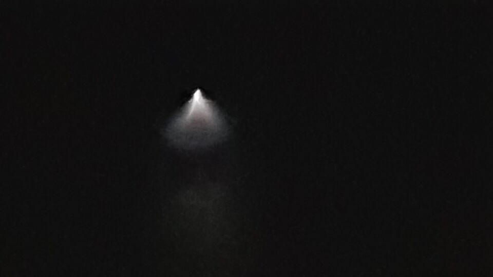 Langzaam landende grote lichtbundel boven wolk foto