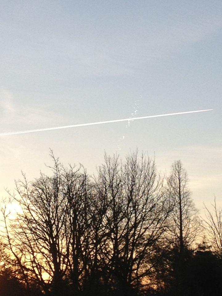 Vliegtuigspoor met daarachter witte lijnen (letters?) foto