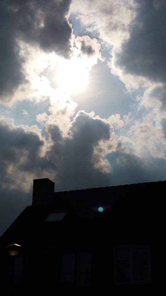 Groene bol tussen de wolken komt naar beneden foto