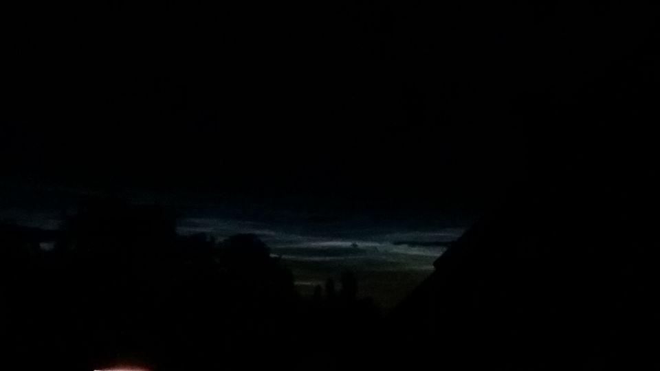 Enorm oplichtend en fel blauwe luchtbaan tijdens donkere nacht met voorwerp foto