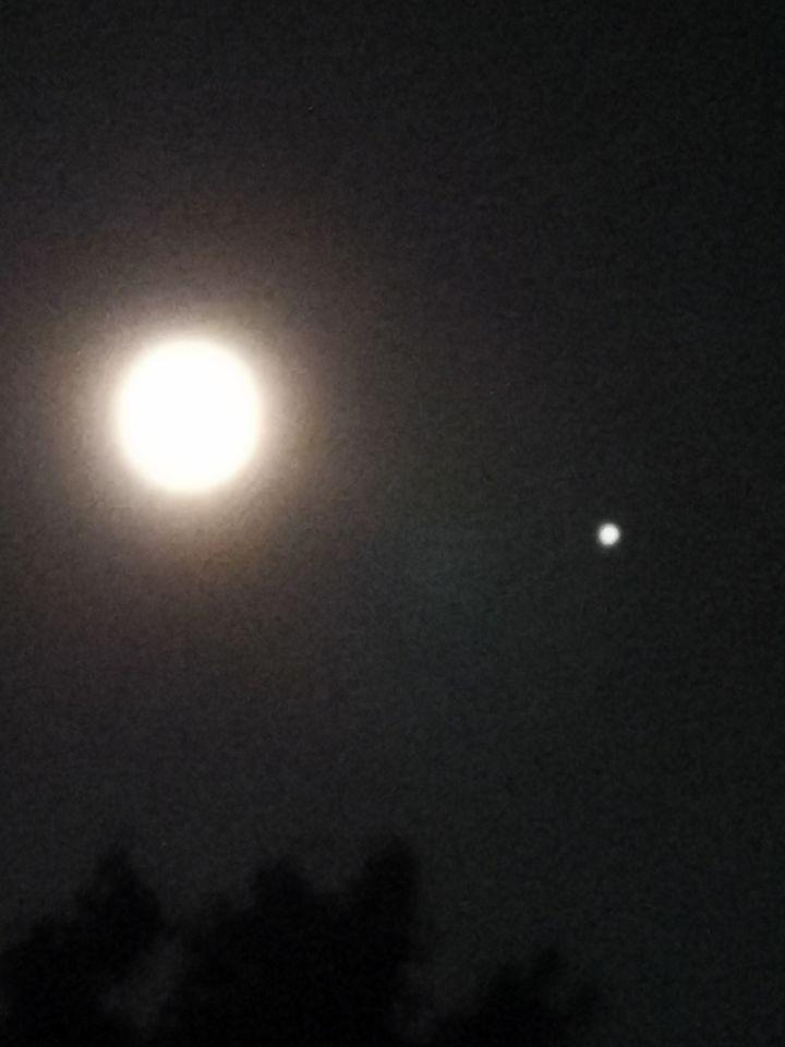 Stilstaande witte bol rechts onder de maan foto